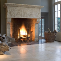 Beautiful country fireplace surround in limestone on a Black Belgian marble border.