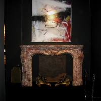 Monumental original vintage fireplace surround in combination wit modern artwork.